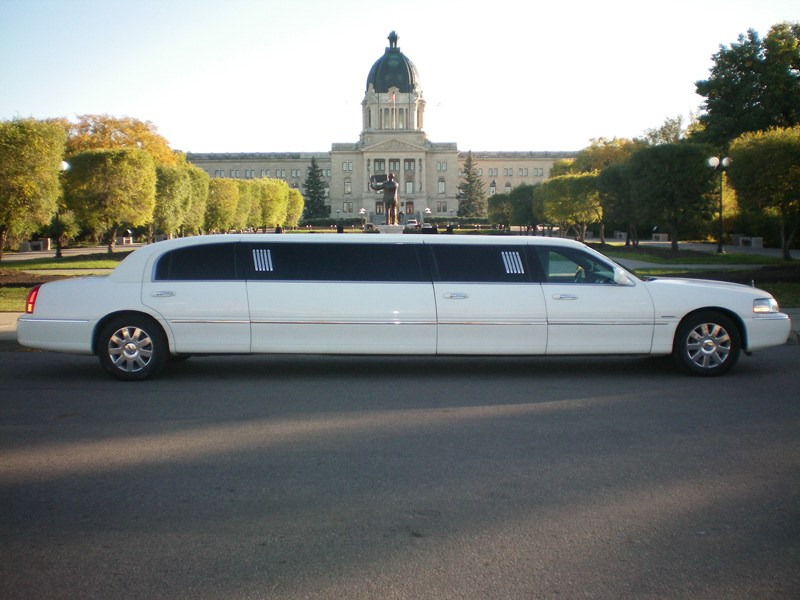 White limousine with view of large building in background
